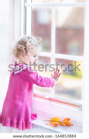 Cute toddler girl in a pink dress watching out of a window with autumn trees view