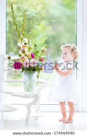 Cute toddler girl in a white dress watering flowers next to a big window with garden view - stock photo
