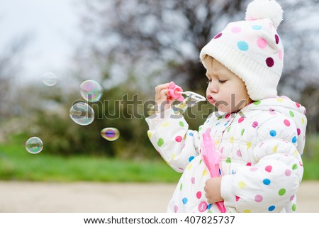 cute toddler girl is blowing soap bubbles