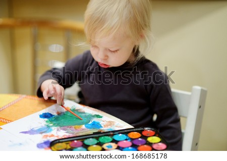 Cute toddler girl is drawing with paints in preschool - stock photo