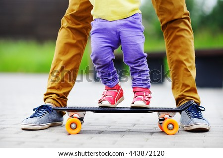 Cute toddler girl learning to skateboard with her father close up outdoors