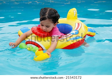 cute toddler girl on inflatable plane in swimming pool - stock photo