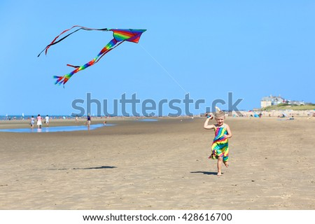 Cute toddler girl playing on the beach flying colorful kite. Child enjoying summer day  at the north sea. Family vacation concept. - stock photo