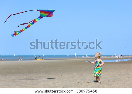 Cute toddler girl playing on the beach flying colorful kite. Child enjoying summer family vacation at the sea. - stock photo