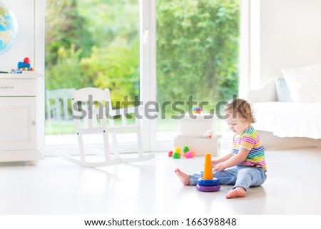 Cute toddler girl playing with a pyramid toy in a white room with a big window with garden view - stock photo