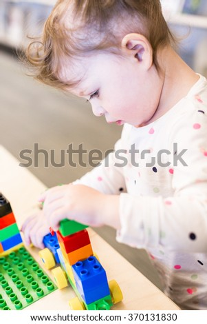 Cute toddler girl playing with bright blocks.