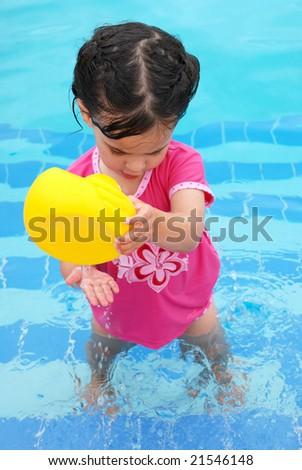 cute toddler girl playing with rubber ducky in swimming pool - stock photo