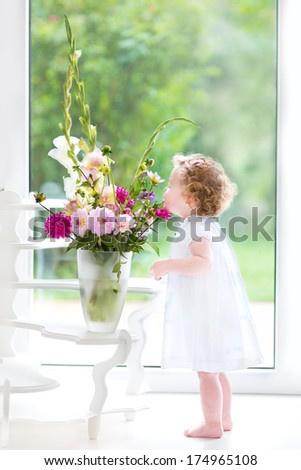 Cute toddler girl smelling fresh flowers at home next to a big window with garden view - stock photo