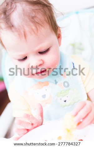 Cute toddler girl wating lunch in her high chair.