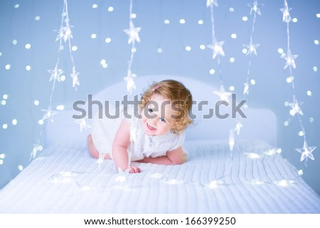 Cute toddler girl with curly hair wearing a white dress playing on a white bed between Christmas lights in blue color