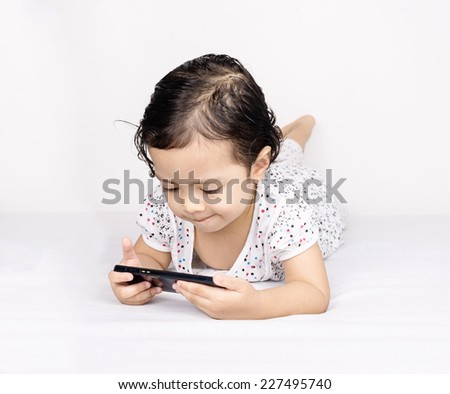 Cute toddler girl with funny face expression when holding and looking at a smartphone or cellular phone while laying on bed - stock photo