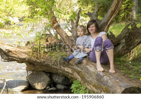 cute toddler girl with her mother in  sitting on a tree over a stream - stock photo