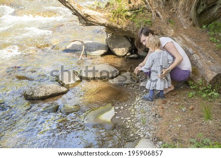 cute toddler girl with her mother in  throwing scree in the stream