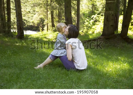 cute toddler girl with her mother palying in the forest - stock photo