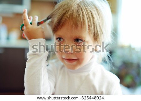 Cute toddler girl with scissors wants to cut hair - stock photo
