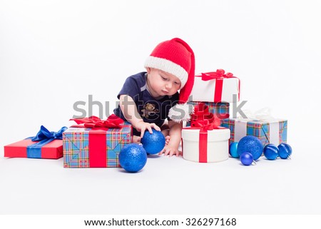 cute toddler is sitting in a New Year's cap among Christmas toys and blue and red boxes with gifts and looking at the camera with a smile on his face, picture with depth of field - stock photo