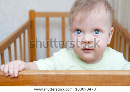 Cute toddler looking out of the crib
