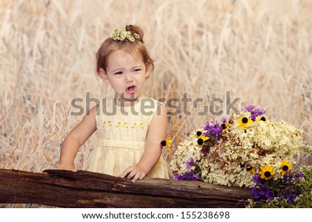Cute toddler making a very sour face expression for her outdoor portraits - stock photo