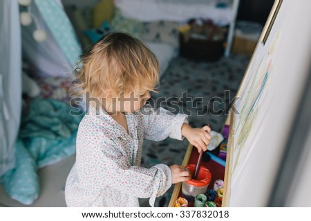 Cute toddler painting with gouache paints in the baby room indoors - stock photo