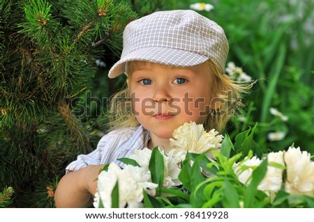 Cute toddler playing in the garden surrounded by flowers