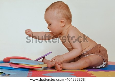 Cute toddler playing with foam puzzle and sitting on the colored mats. Active baby wearing cloth diaper. Isolated. - stock photo