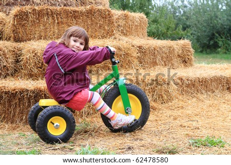 Cute toddler riding her bike on the farm