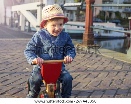 Cute toddler riding his tricycle in Amsterdam - stock photo