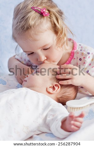 Cute Toddler sister kisses newborn brother - stock photo