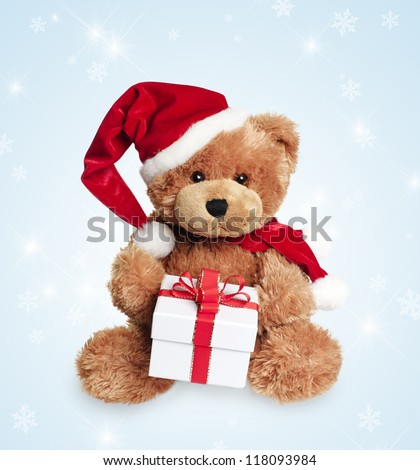 Cute toy bear with christmas gift and santa hat on light background