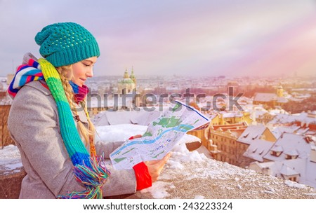 Cute traveler girl searching right direction on the map, standing on the roof of building and enjoying beautiful winter cityscape, travel to Prague
