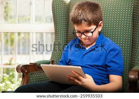 Cute tween wearing glasses and playing video games on a tablet computer at home