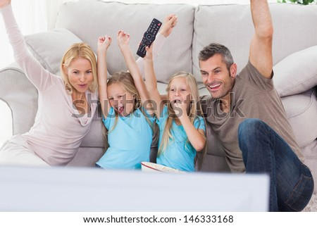 Cute twins and parents raising arms while watching television sitting on a carpet - stock photo
