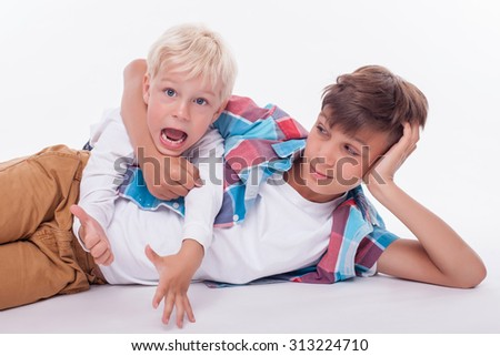 Cute two brothers are lying on flooring and making fun. The elder boy is embracing the neck of his brother and smiling. The small boy is screaming and looking forward with disappointment. Isolated - stock photo