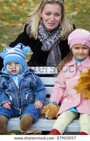 cute two kids at bench with mom - stock photo