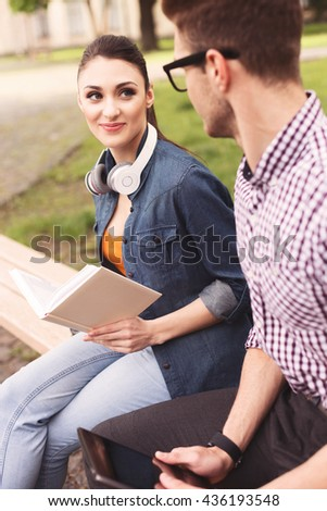 Cute two students are studying together outdoors - stock photo
