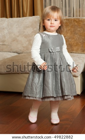 Cute two-year-old girl in a fancy gray dress standing in home interior