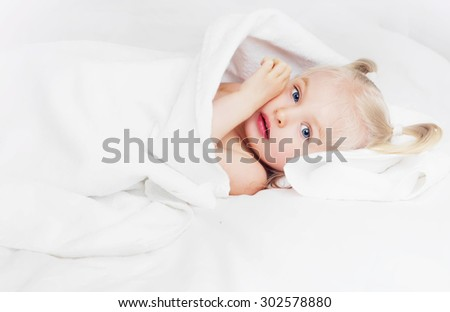 cute two year old girl wrapped into towels after taking a bath  - stock photo