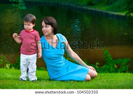 Cute two years old boy with his young mom in park - stock photo