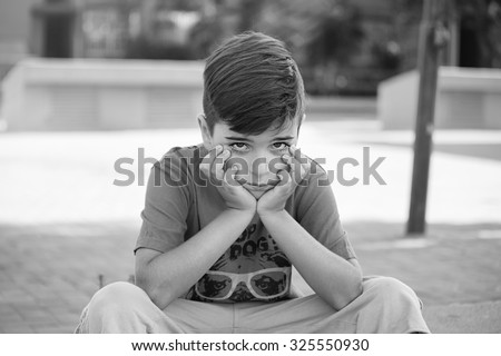 Cute upset boy pouting in the park on a sunny day - stock photo