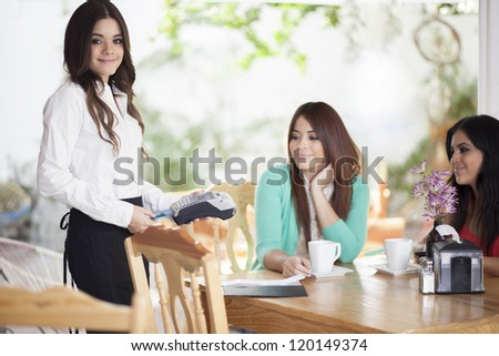 Cute waitress charging customers with a credit card terminal