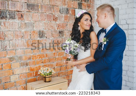cute wedding couple in the interior studio decorated red brick. hey kiss and hug each other