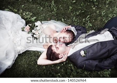 Cute Wedding couple in the outdoors arms around each other on the grass looking at each other. - stock photo