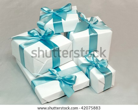 Cute white gift boxes with blue ribbon - stock photo