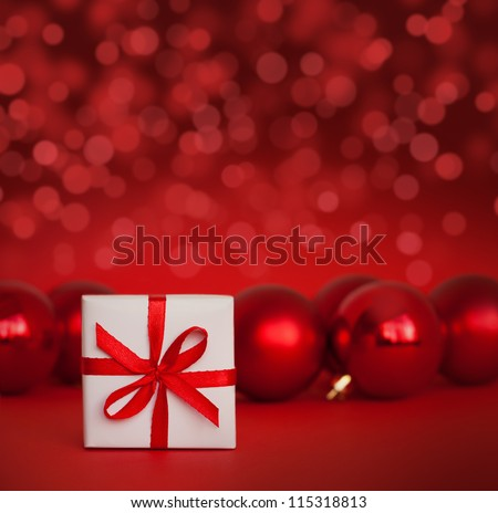 Cute white gift with red christmas balls on red abstract light background