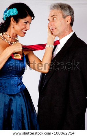 Cute white mature couple in romantic moment with formal dress, while she playfully pulls on his red tie