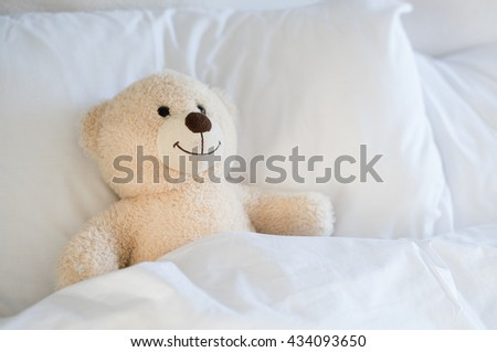 Cute white teddy bear in kids room. Teddy bear leaning on pillow in the child bed. A cute teddy bear lying in bed under the sheets. - stock photo