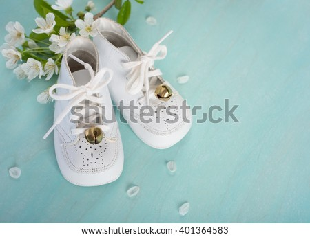 Cute, White Vintage Leather Infant Baby Shoes with spring flowers on Cyan Turquoise Faux Painted, Rustic wood Board Background with room or space for copy, text, your words.  Horizontal aerial view
