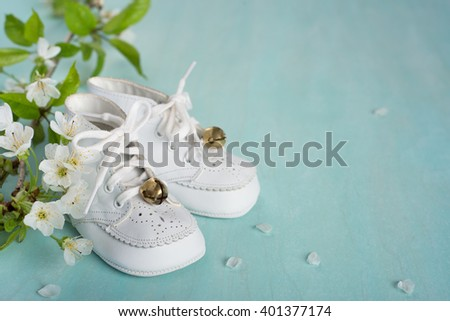 Cute, White Vintage Leather Infant Baby Shoes with spring flowers on Cyan Turquoise Faux Painted Rustic wood Board Background and room or space for copy, text, your words. Horizontal side bottom view - stock photo