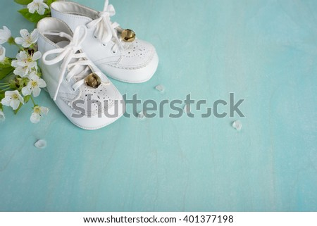 Cute, White Vintage Leather Infant Baby Shoes with spring flowers on Cyan Turquoise Faux Painted, Rustic wood Board Background with room or space for copy, text, your words.  Horizontal aerial view - stock photo