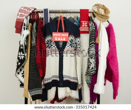 Cute winter sweaters displayed on hangers with a big Christmas sale sign. Season clearance rack with colorful winter clothes and accessories. - stock photo